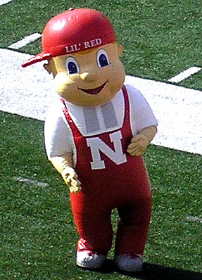Lil' Red burst on the scene of the Nebraska sideline in 1993. Lil' Red was born of the vision of Assistant Athletic Director Barbara Hibner, who fashioned the character after an Omaha Lancer mascot. Intended to appeal to children, Lil' Red is known for his many antics. He dances, stands on his head and even makes his head disappear. Lil' Red is an 8-foot inflatable figure. He landed a spot in the Mascot Hall of Fame in 2007.  -OWH, 2003